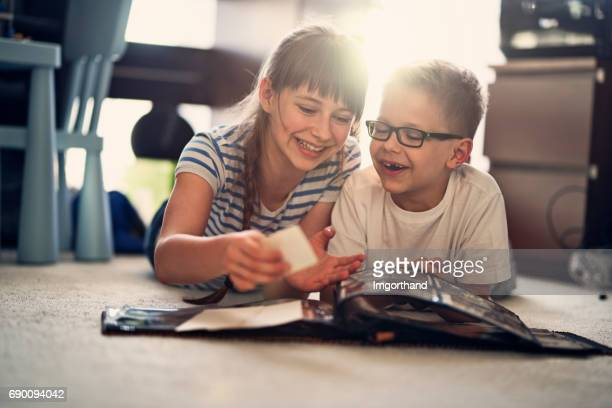 brother and sister looking at photo album - photo album stock photos and pictures