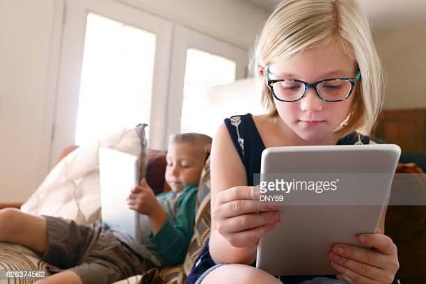 Brother And Sister Looking At Their Respective Digital Tablets