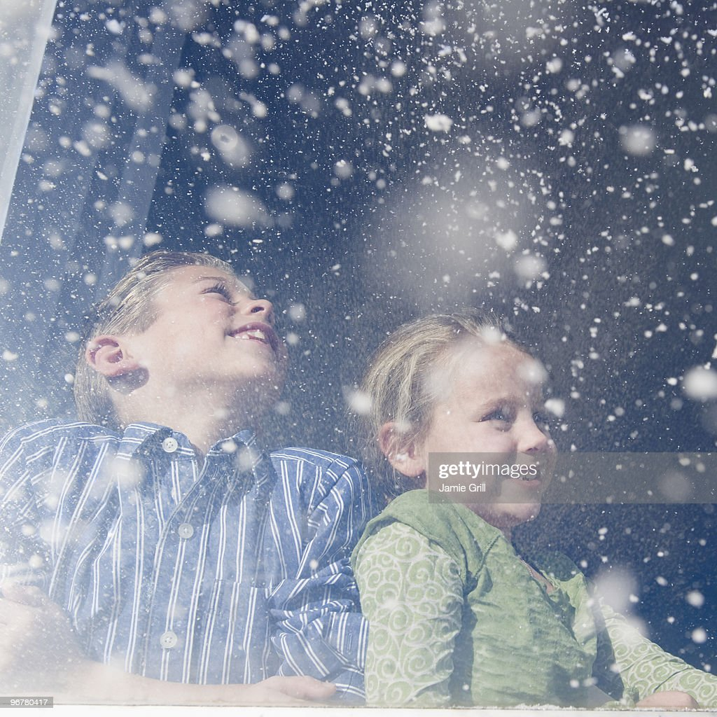 Brother and sister looking out window at snow : Stock Photo