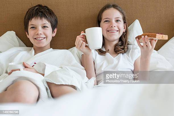 Brother and sister lying in bed eating breakfast