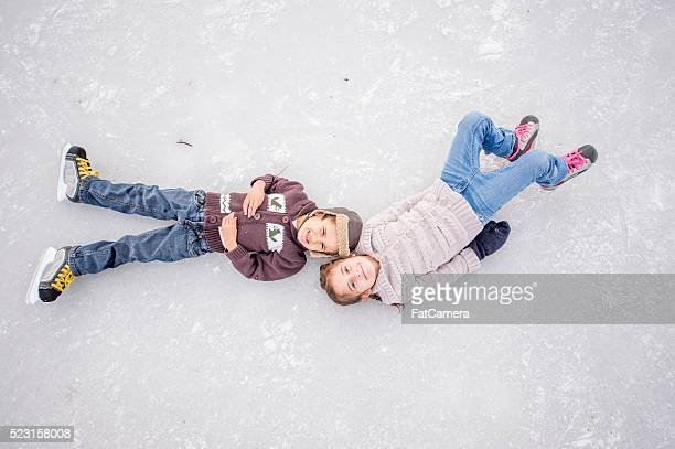 brother and sister lying on a frozen pond - ice skate stock pictures, royalty-free photos & images