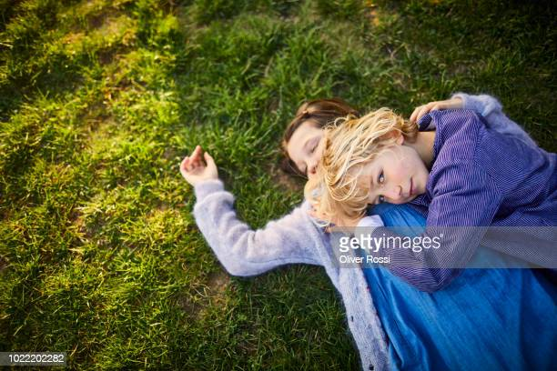 brother and sister lying on a meadow - linda oliver fotografías e imágenes de stock
