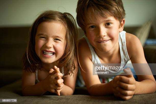Brother and sister lying on floor smiling happily