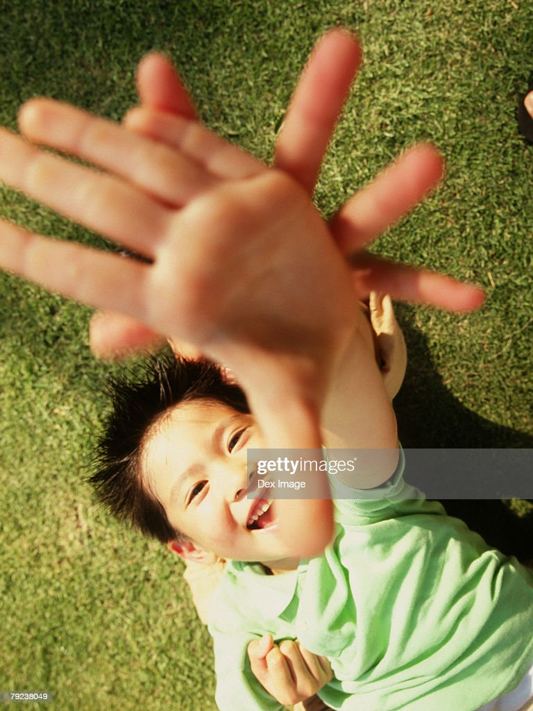 Brother and sister lying on grass, arms stretched : Stock Photo