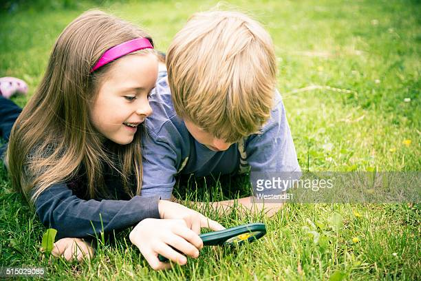 Brother and sister lying on meadow watching flowers with magnifying glass