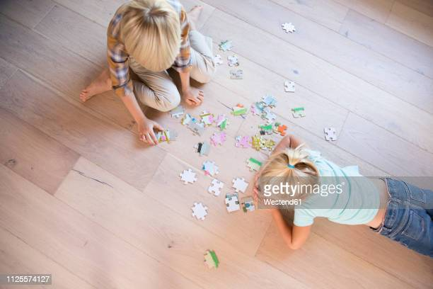 brother and sister lying on the floor at home playing jigsaw puzzle - puzzle stock-fotos und bilder