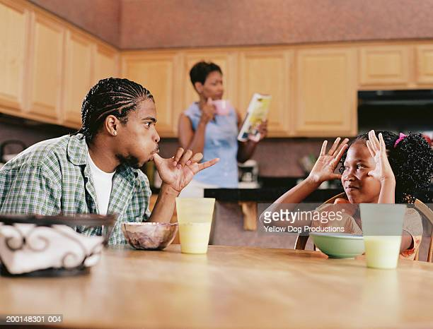 Brother and sister (8-18) making funny gestures at kitchen table