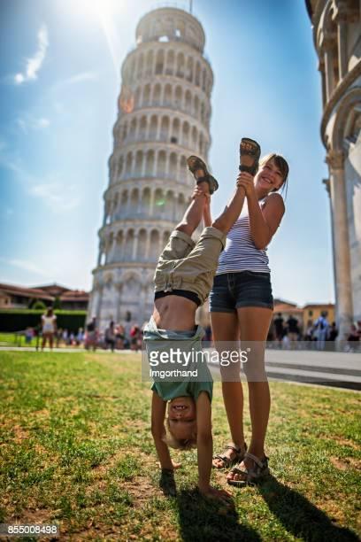 broer en zus maken grappige foto's van de scheve toren van pisa - pisa stockfoto's en -beelden