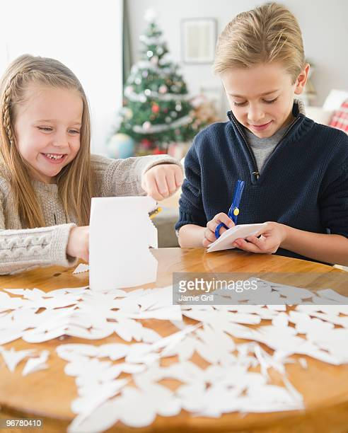 Brother and sister making paper snowflakes