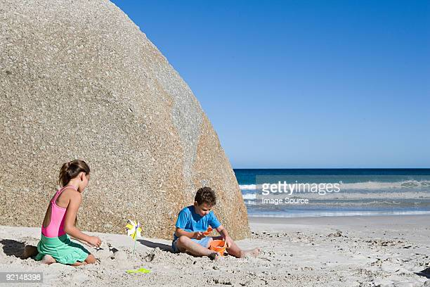 Brother and sister making sandcastles in front of boulder on the beach