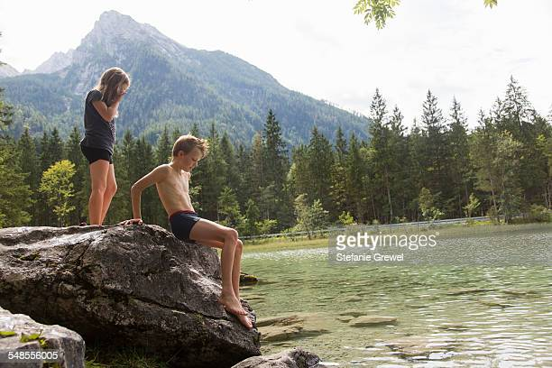 brother and sister on lake boulder, hintersee, zauberwald, bavaria, germany - zwembroek stockfoto's en -beelden