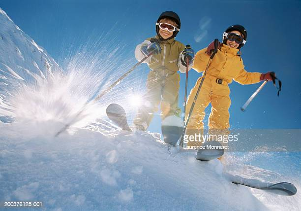 brother and sister (8-12) on ski slope, smiling, low angle view - スキー板 ストックフォトと画像