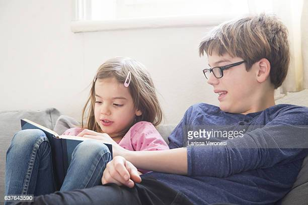 Brother and sister on sofa reading book