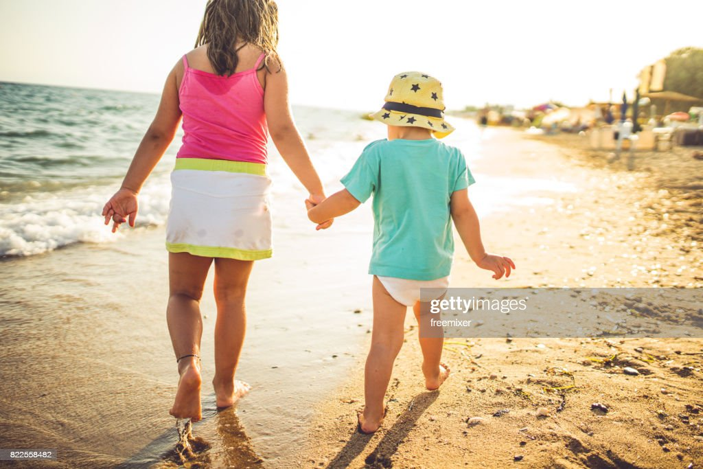 Brother and sister on the beach : Stock Photo