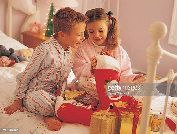 brother and sister opening presents from their christmas stockings on christmas morning - stockings no shoes stock pictures, royalty-free photos & images