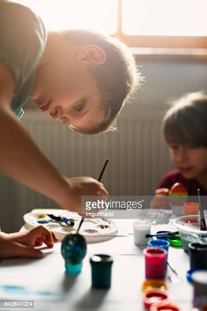 brother and sister painting easter eggs - dirty easter stock pictures, royalty-free photos & images
