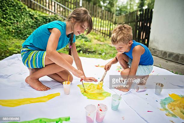 Brother and sister painting outdoors
