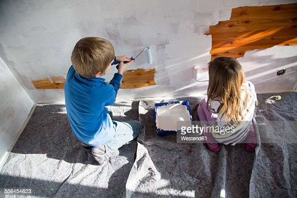 Brother and sister painting wooden wall