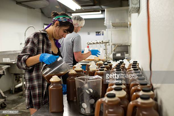 Brother and sister partners Amy and Peter Rothstein fill bottles of their chai tea concentrate in the Dona Chai kitchen space at the Organic Food...