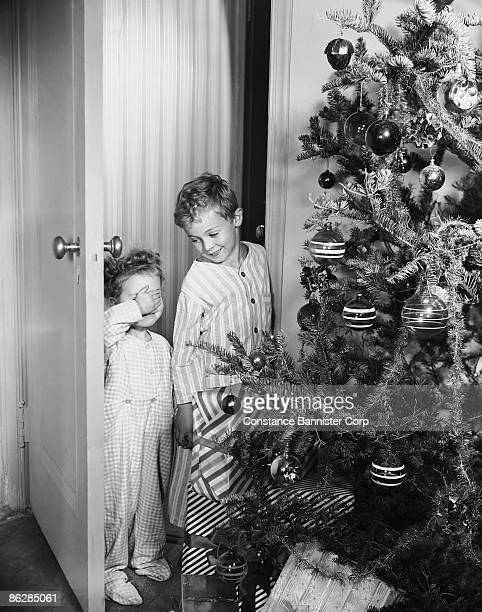 brother and sister peeking at gifts under christmas tree - noel noir et blanc photos et images de collection