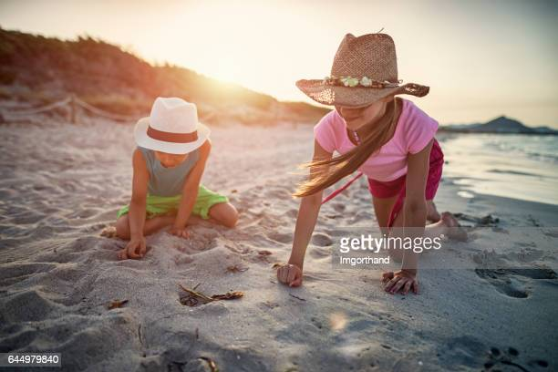Brother and sister picking up sea shells at the beach