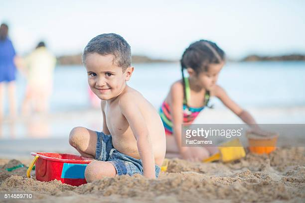 Brother and Sister Placing on a Sandy Beach