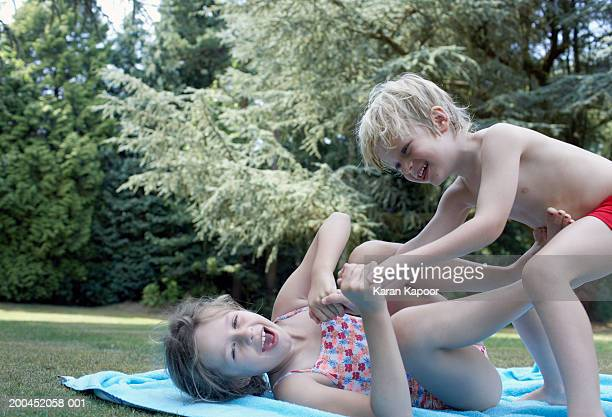 Brother and sister (4-9) play fighting in garden, smiling