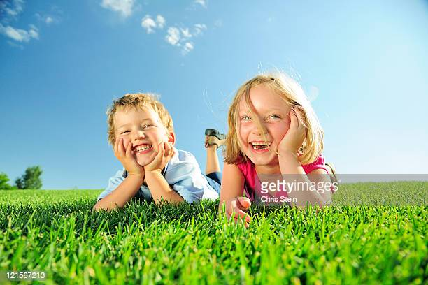 Brother and sister play in the grass