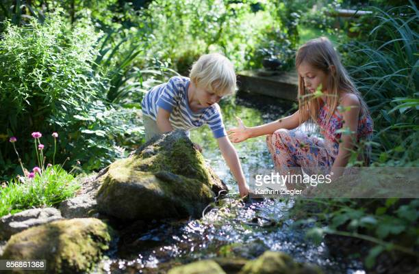 brother and sister playing by a stream in the garden - bach stock-fotos und bilder