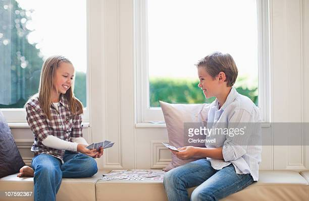 Brother (10-11) and sister (8-9) playing cards at home