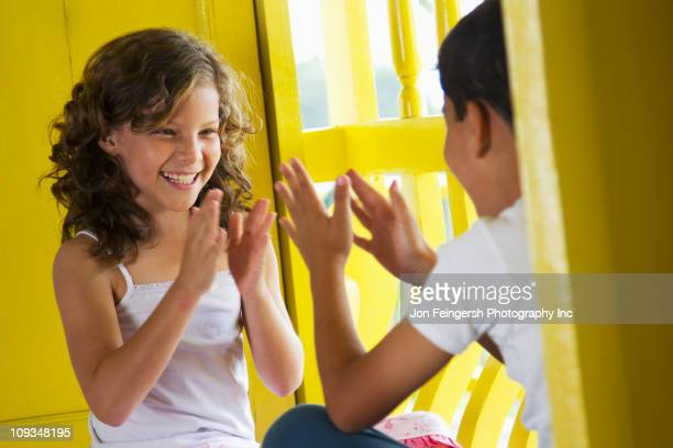 Brother and sister playing clapping game