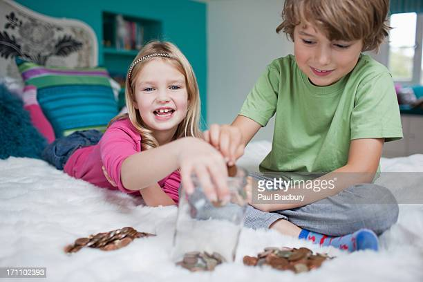 Brother and sister playing counting money in bedroom