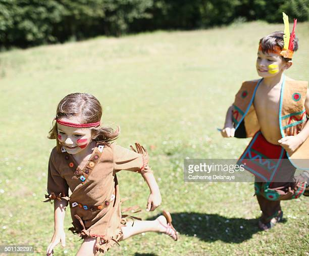 A brother and sister playing, disguised as indians