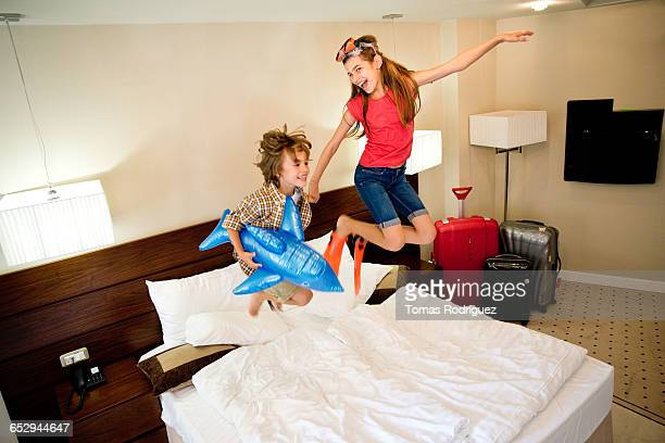 Brother and sister playing in hotel room.