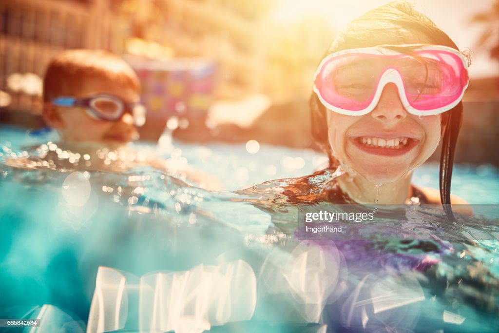 Brother and sister playing in resort pool. : Stock Photo