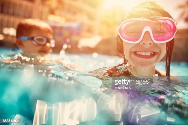 broer en zus spelen in resort zwembad. - sommer stockfoto's en -beelden