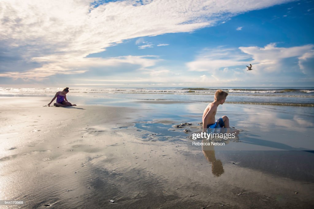 Brother And Sister Playing In Sand At Waters Edge Stock Photo