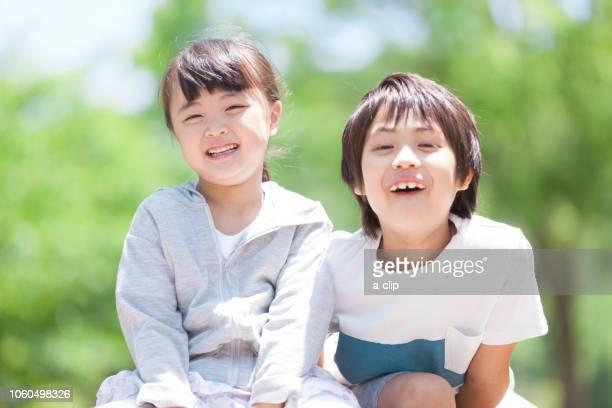 公園で遊ぶ兄妹 - 兄弟 ストックフォトと画像