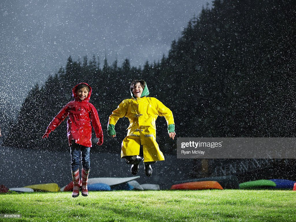 Brother and sister playing in the rain. : Stock Photo