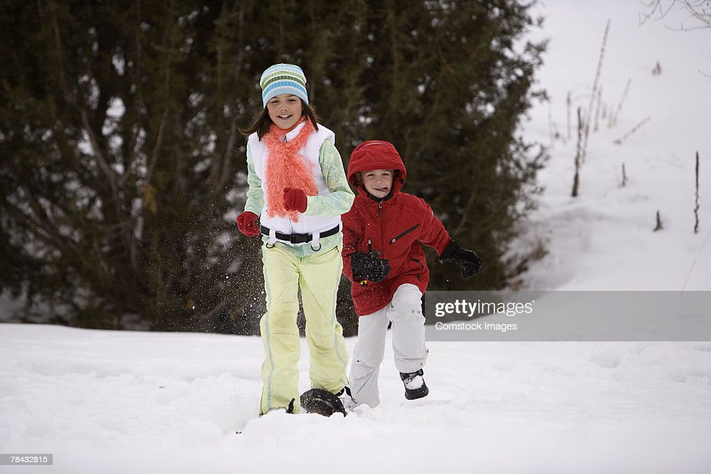 Brother and sister playing in the snow : Stockfoto