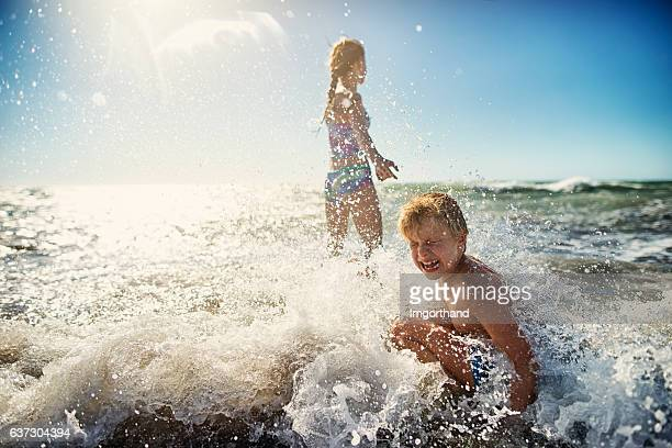 Brother and sister playing in tuscan sea waves