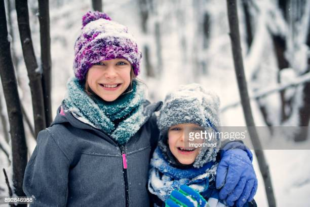 Brother and sister playing in winter forest