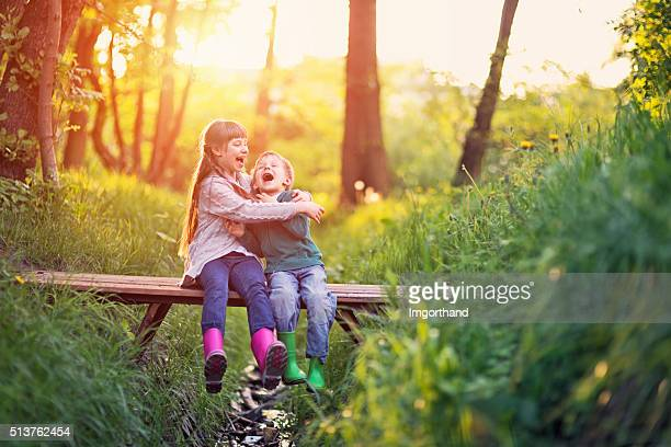 brother and sister playing on bridge in forest - spring flowing water stock pictures, royalty-free photos & images