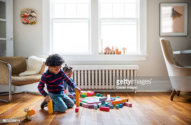 brother and sister playing on floor at home - toy block stock pictures, royalty-free photos & images