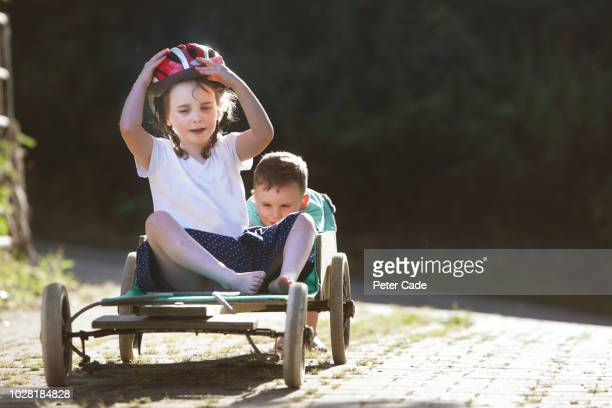 brother and sister playing on homemade go-kart - brother stock pictures, royalty-free photos & images