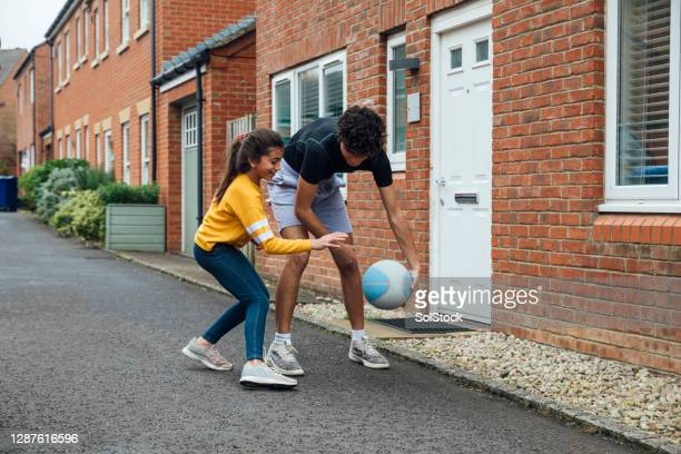 brother and sister playing on the driveway - drive ball sports stock pictures, royalty-free photos & images