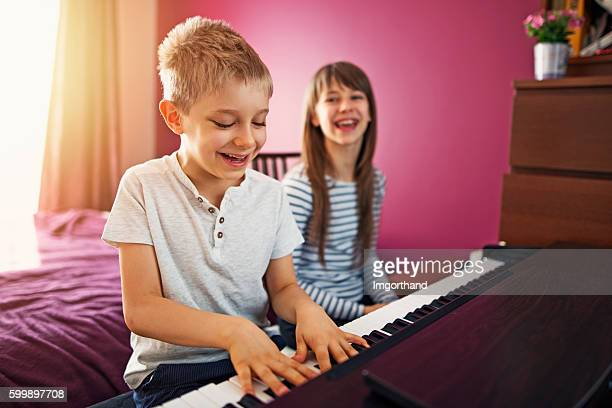 brother and sister playing piano together - electric piano stock photos and pictures