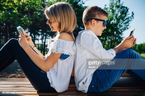 Brother and sister playing smart phones in park