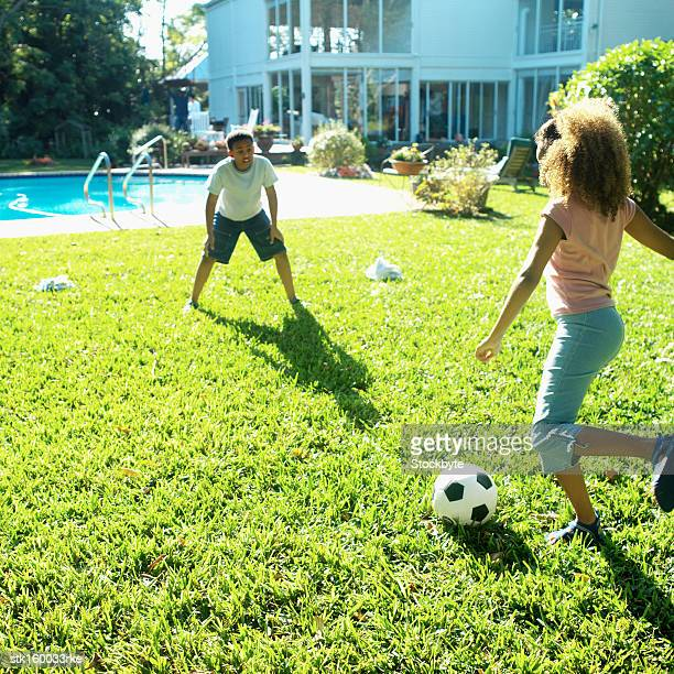 brother (12-13) and sister (8-9) playing soccer in back garden with swimming-pool