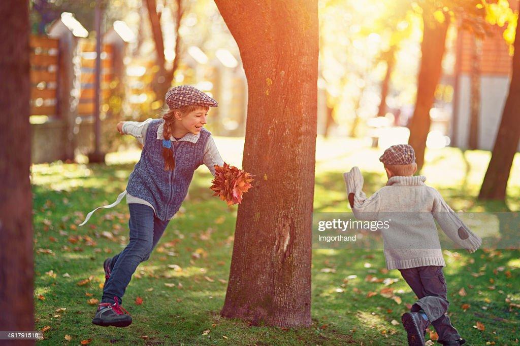Hermano y hermana jugando en el parque otoño etiqueta : Foto de stock